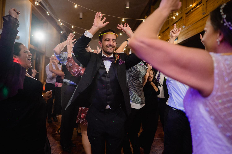 groom wearing glow stick crown dancing with bride and guests solitude resort utah wedding