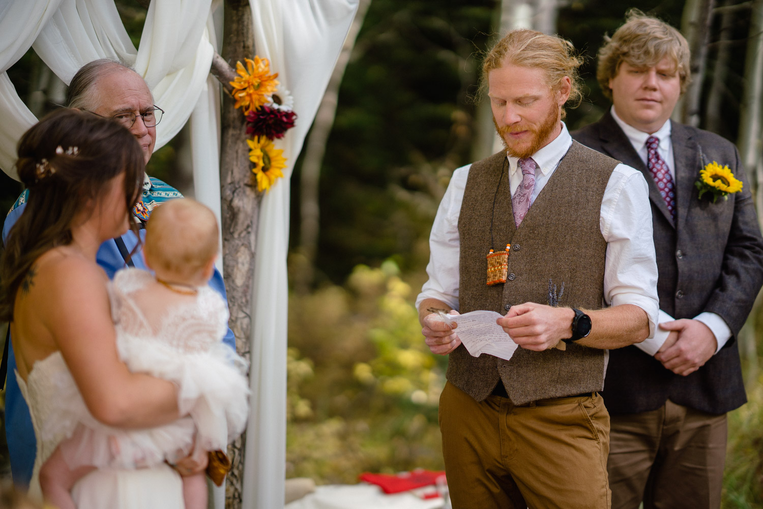 groom reading vows to bride and baby with officiant and best man at outdoor altar
