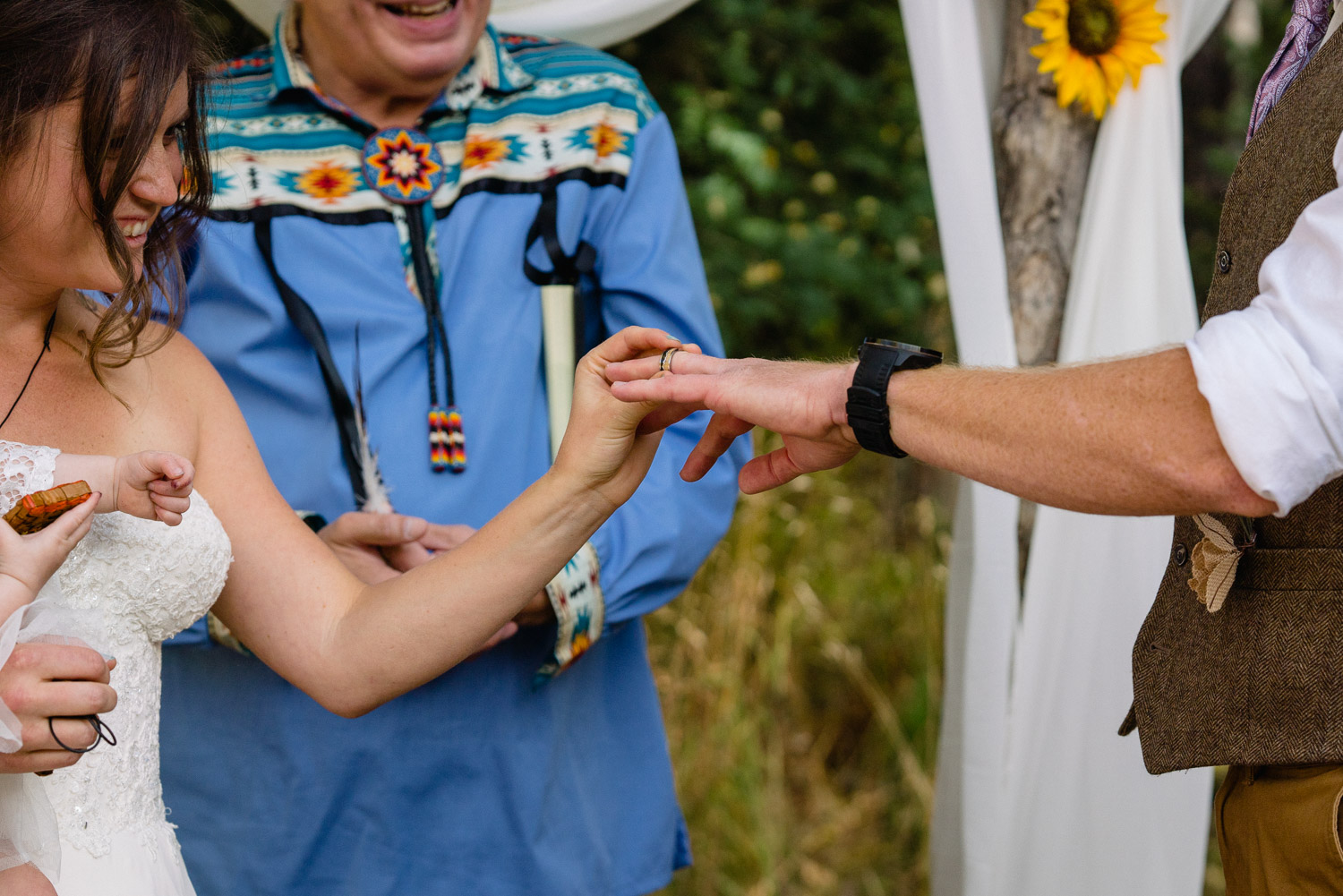 bride putting ring on grooms finger with officiant in background