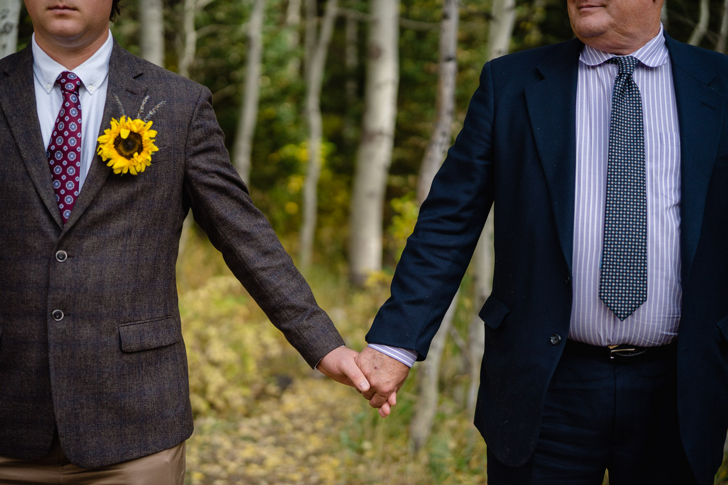 best man and dad holding hands outside aspen trees spruces campground