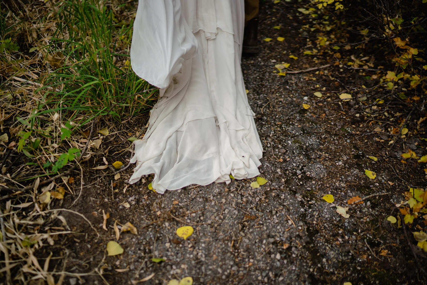 brides dress train outside on gravel spruces campground