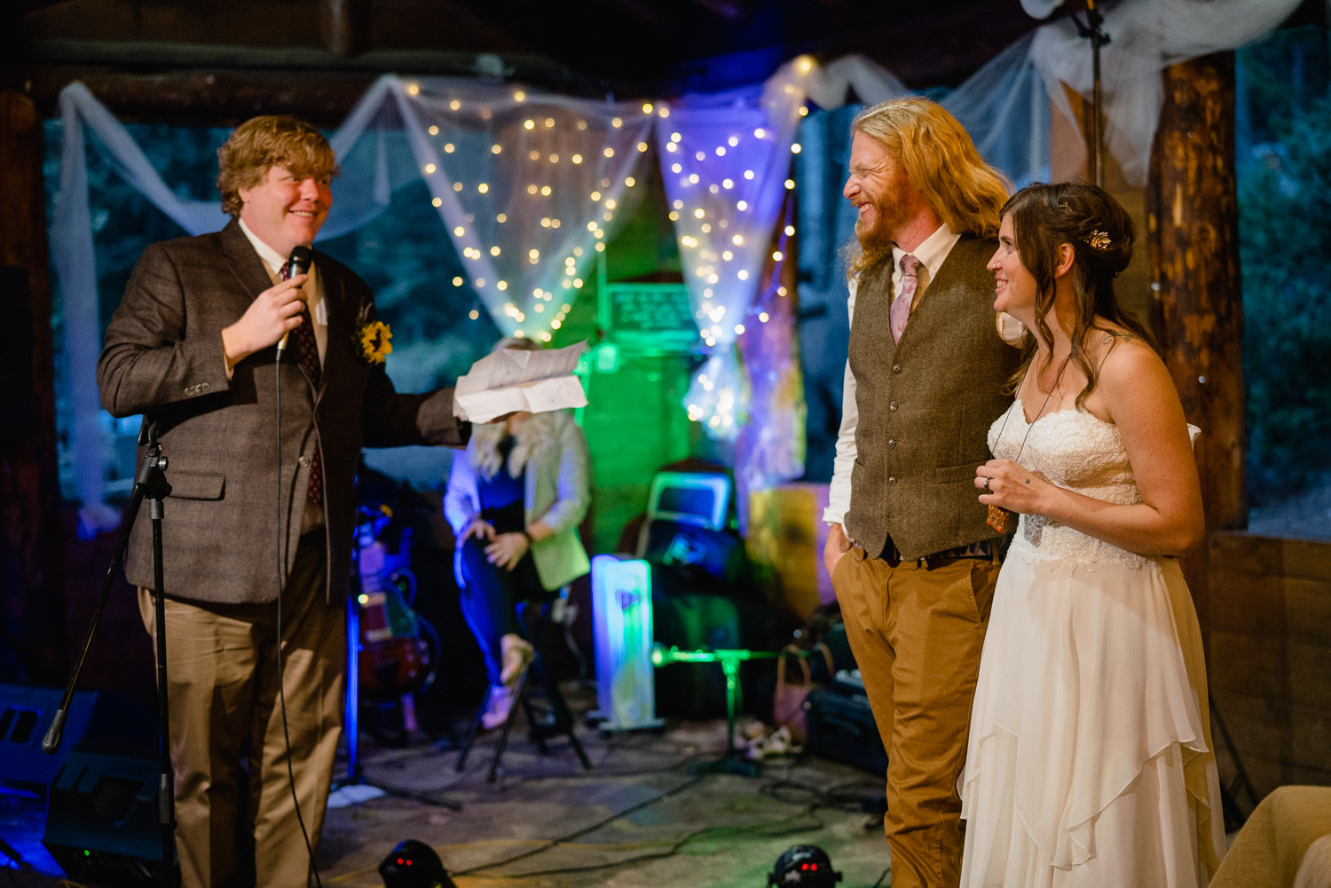 best man giving toast to bride and groom at night campground wedding