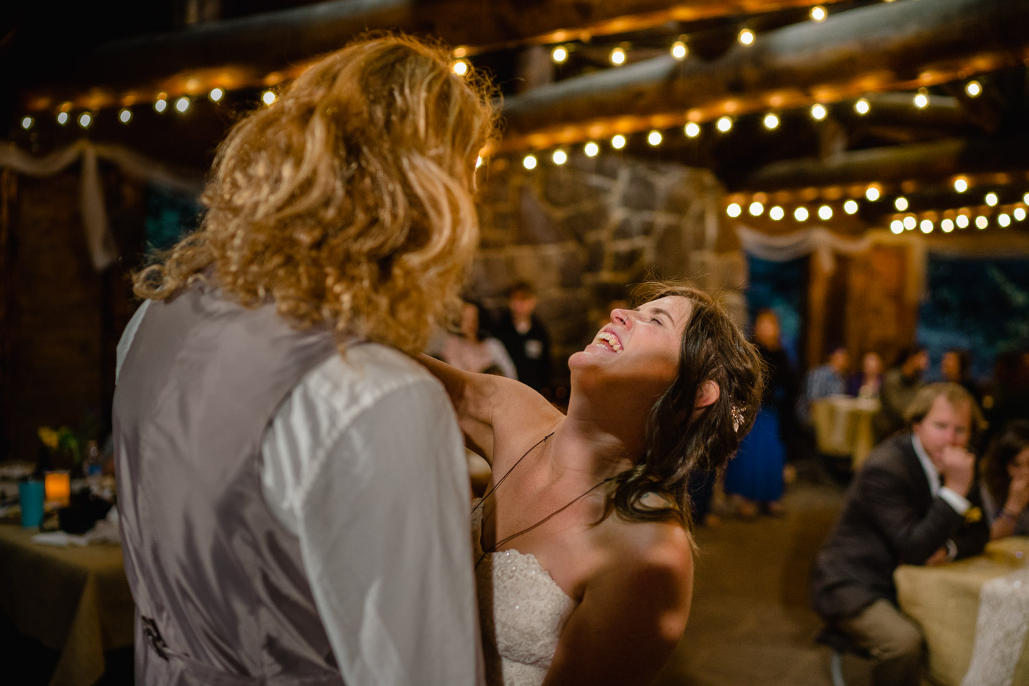 bride and groom dancing and laughing with lights at night campground reception