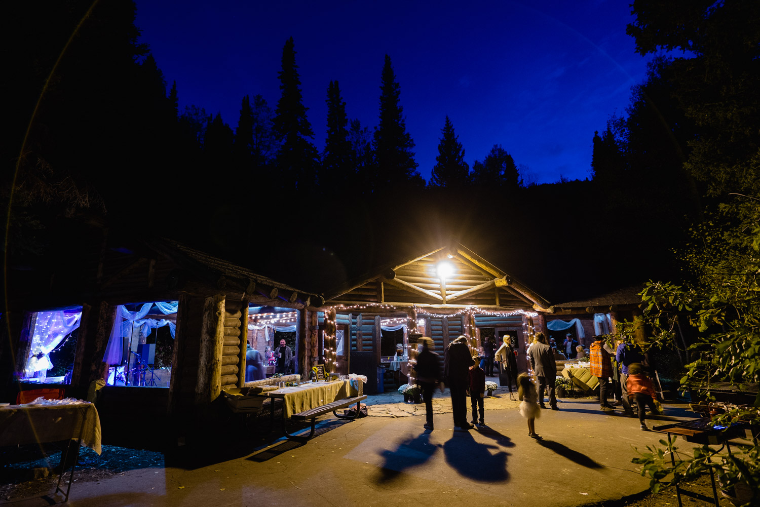 night lit lodge with guests spruces campground