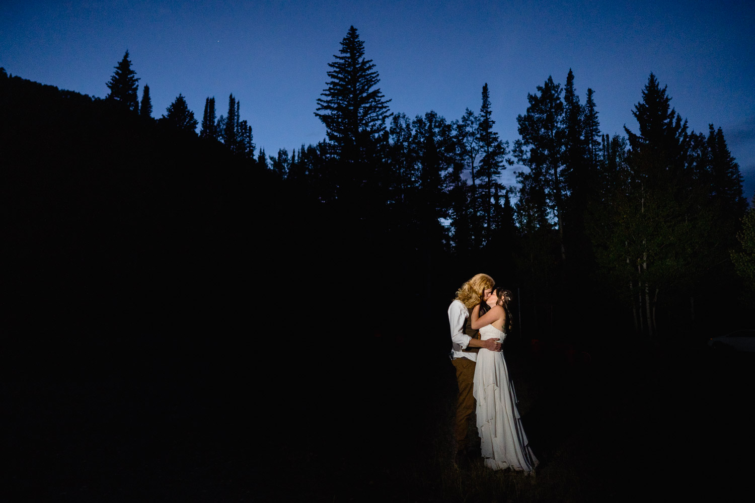 happy couple kissing under night sky tree profile spruces campground