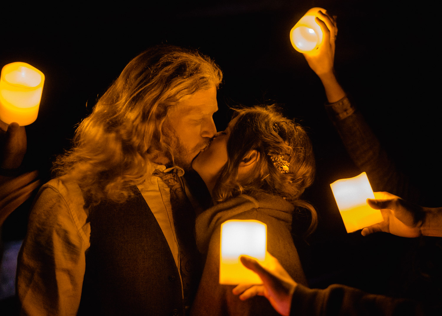 bride and groom kissing surrounded by candlelight campground reception