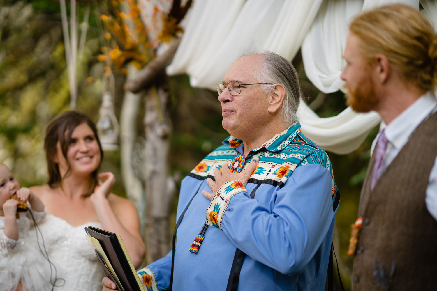 officiant hand over heart with bride and groom outdoor altar