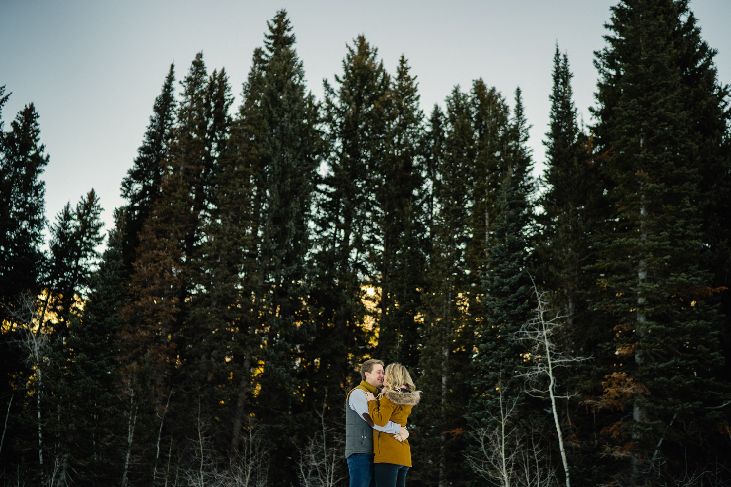 Happy couple hugging in front of tall trees