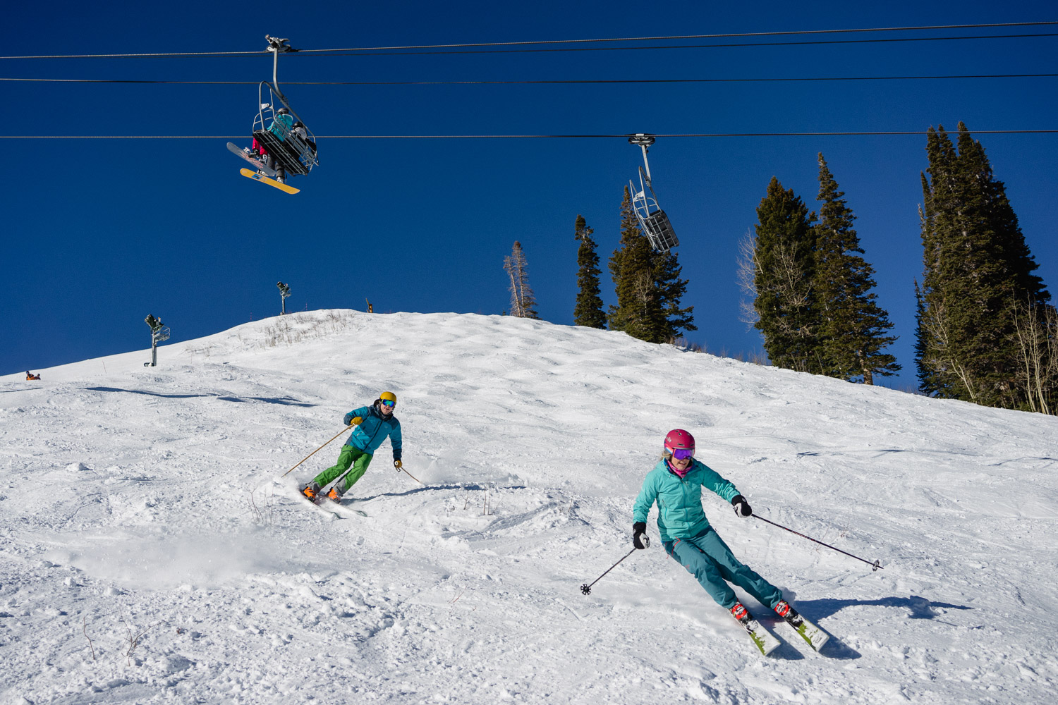 couple skiing under chairlift utah ski resort