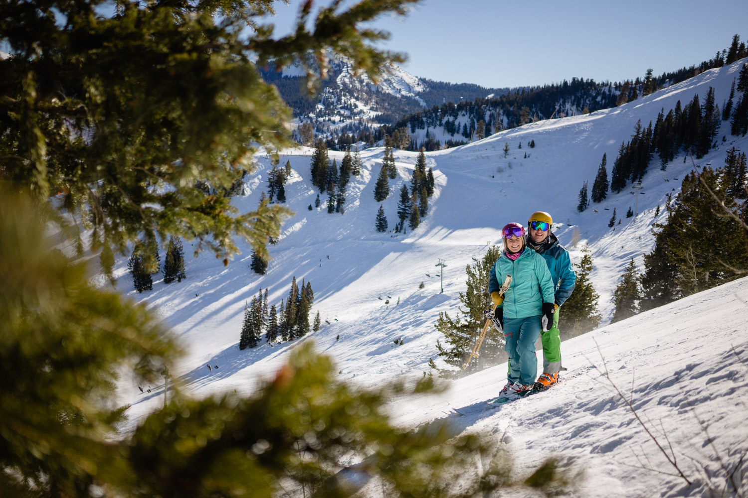 happy skiing couple on snowy mountain with trees
