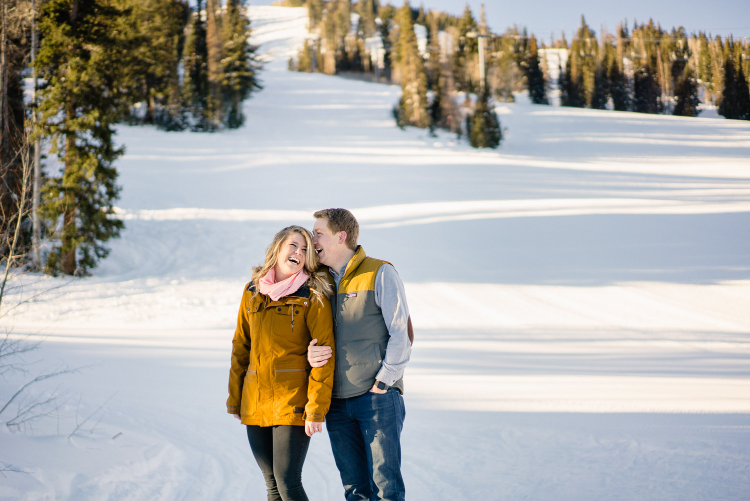 happy engaged couple on snowy mountain with trees