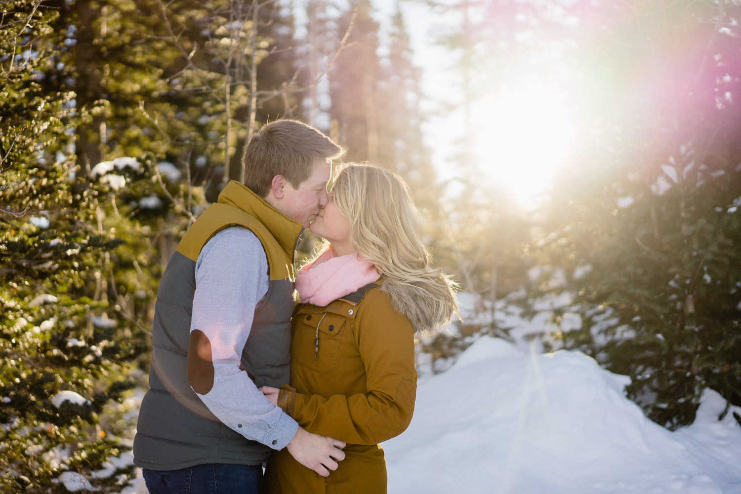 happy couple kissing in snow with trees