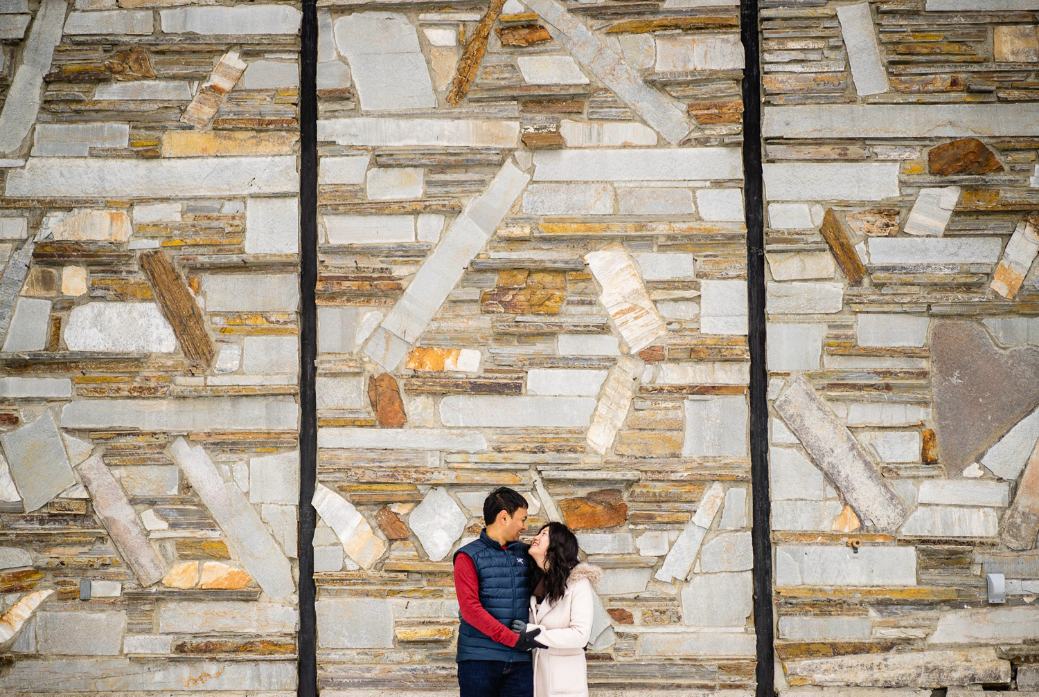 happy couple stone wall backdrop