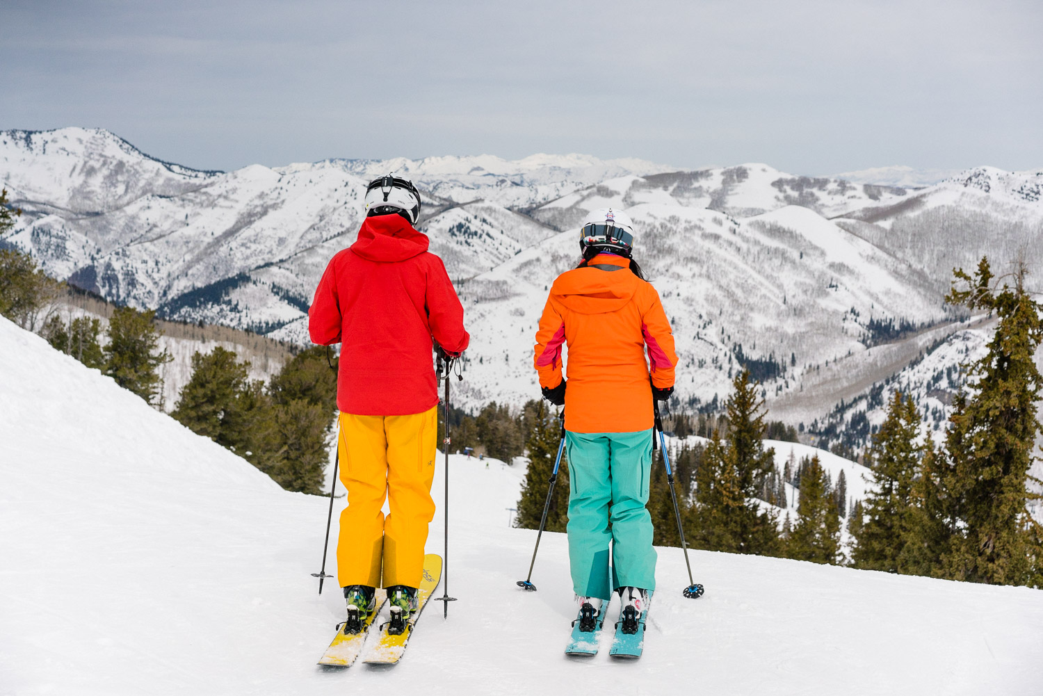 couple looking down snowy mountain at utah ski resort