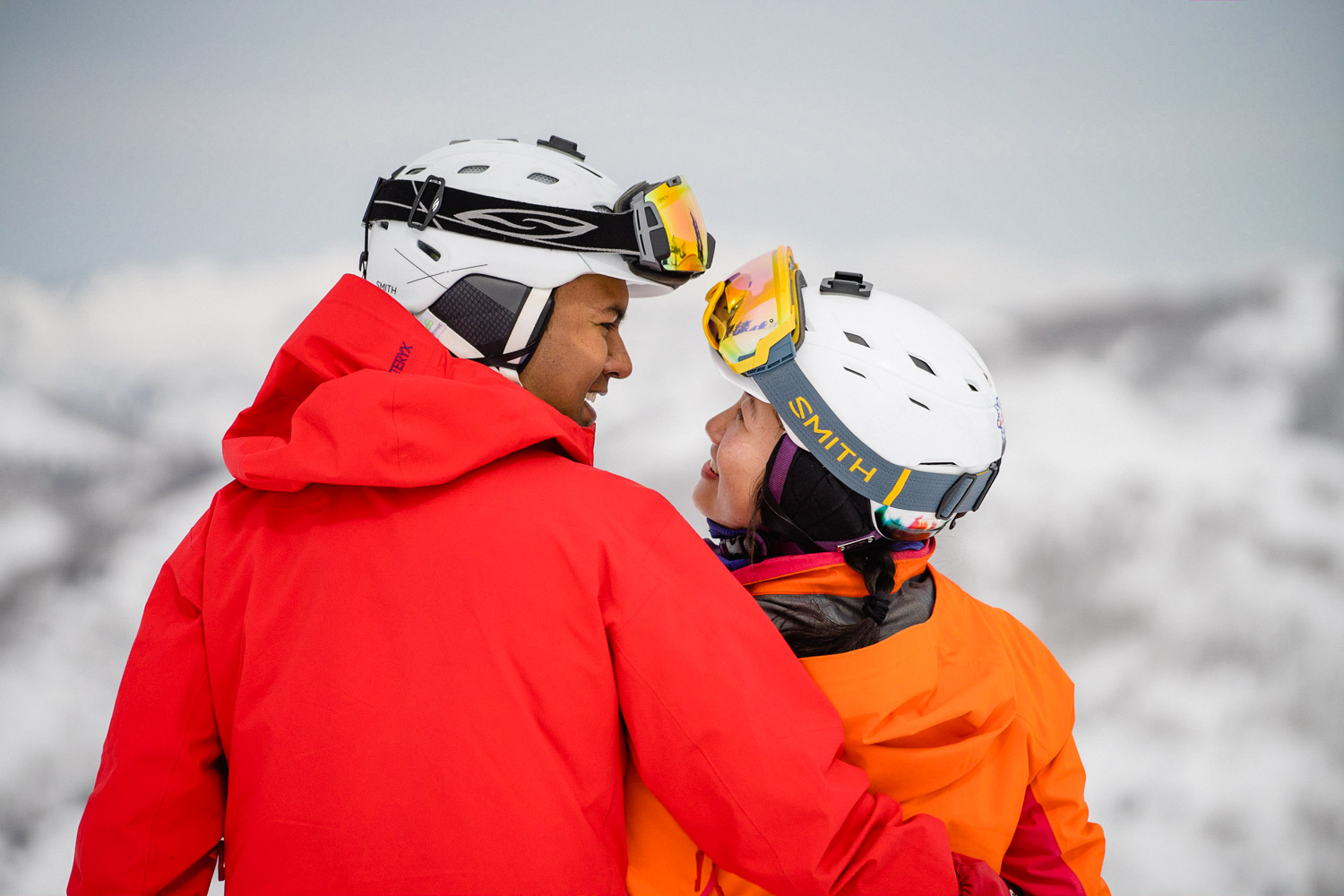 happy couple gazing at each other on snowy mountain utah ski resort