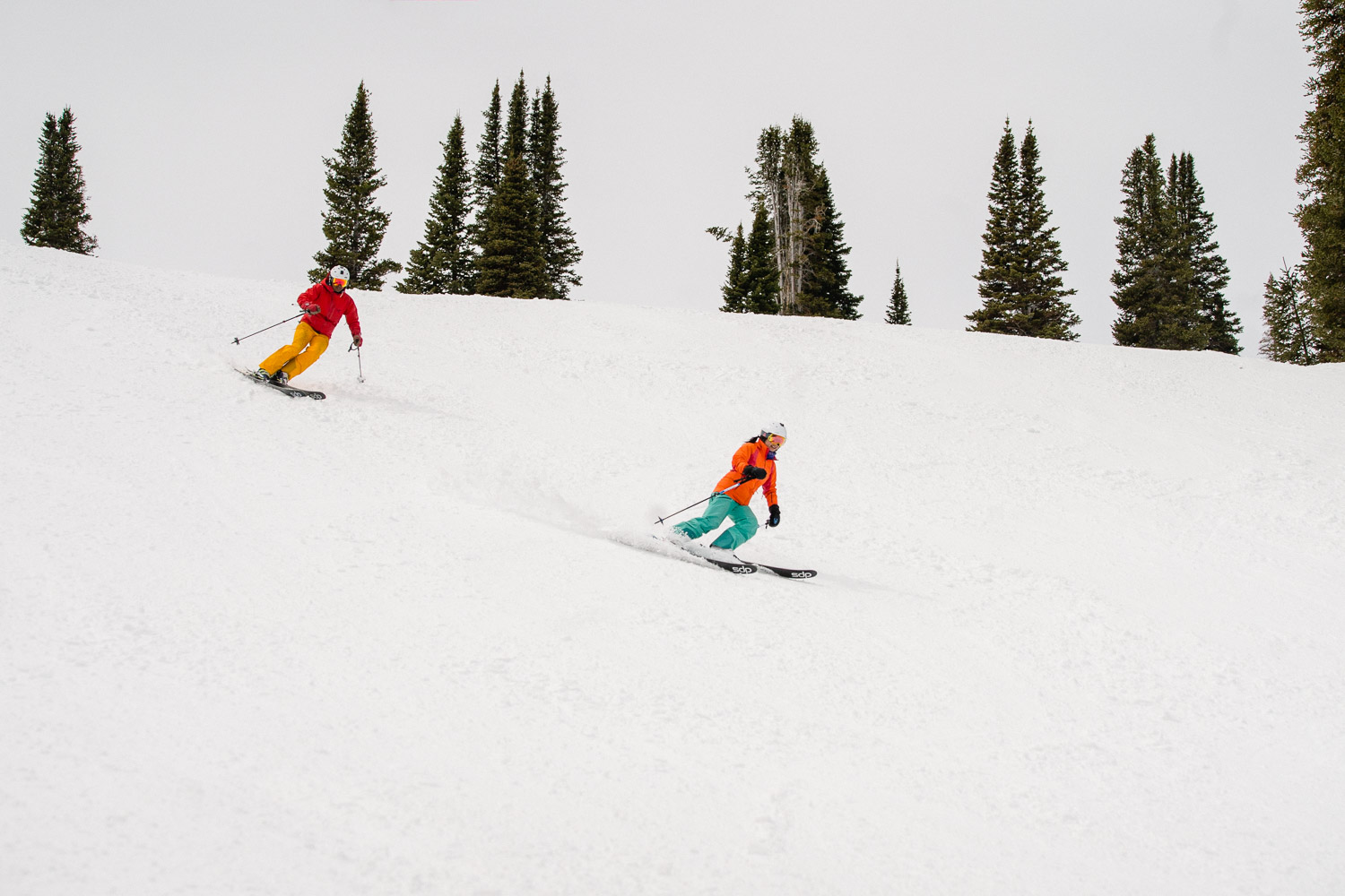 happy couple skiing down groomer at utah ski resort