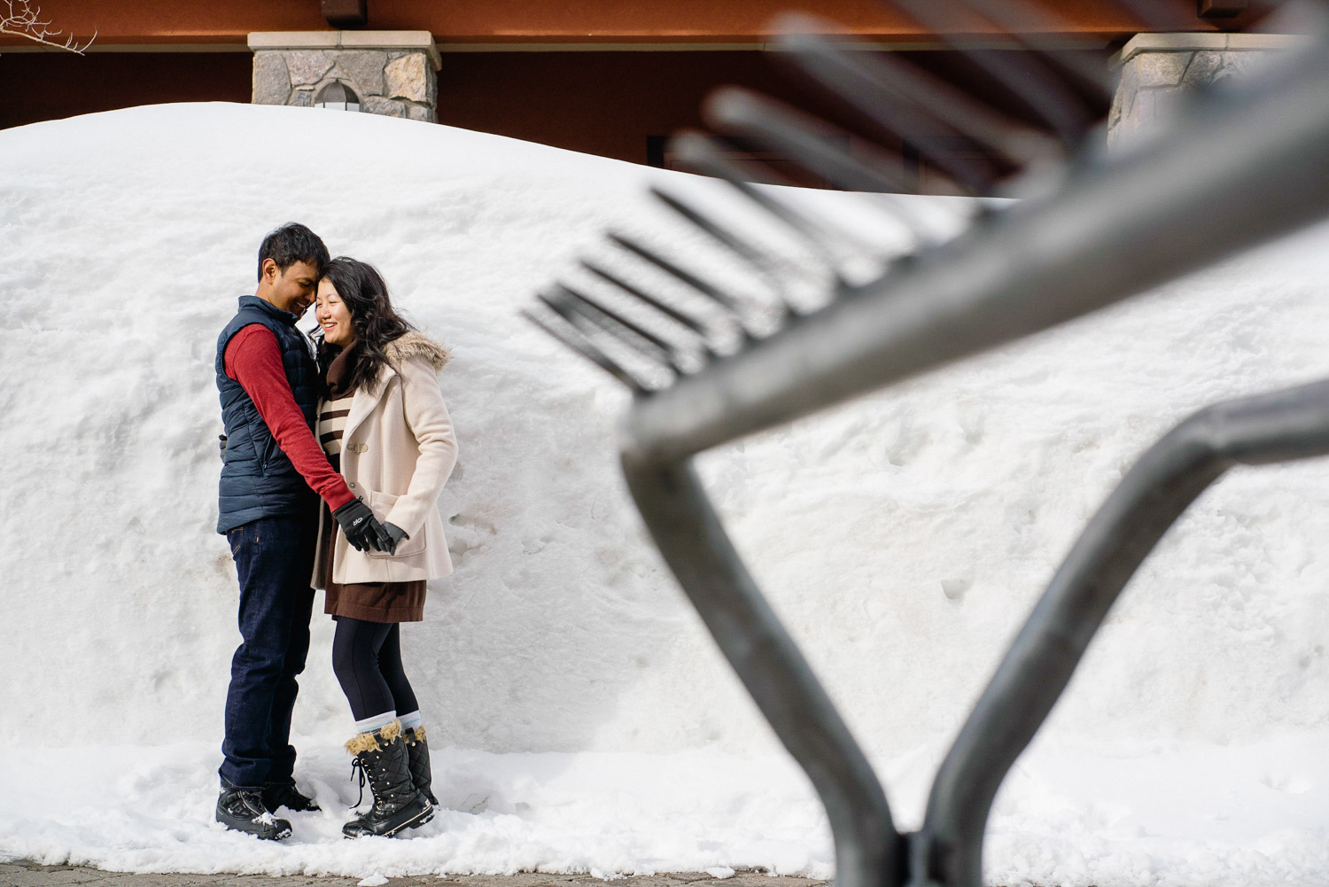 happy couple in front of snow bank at ski resort