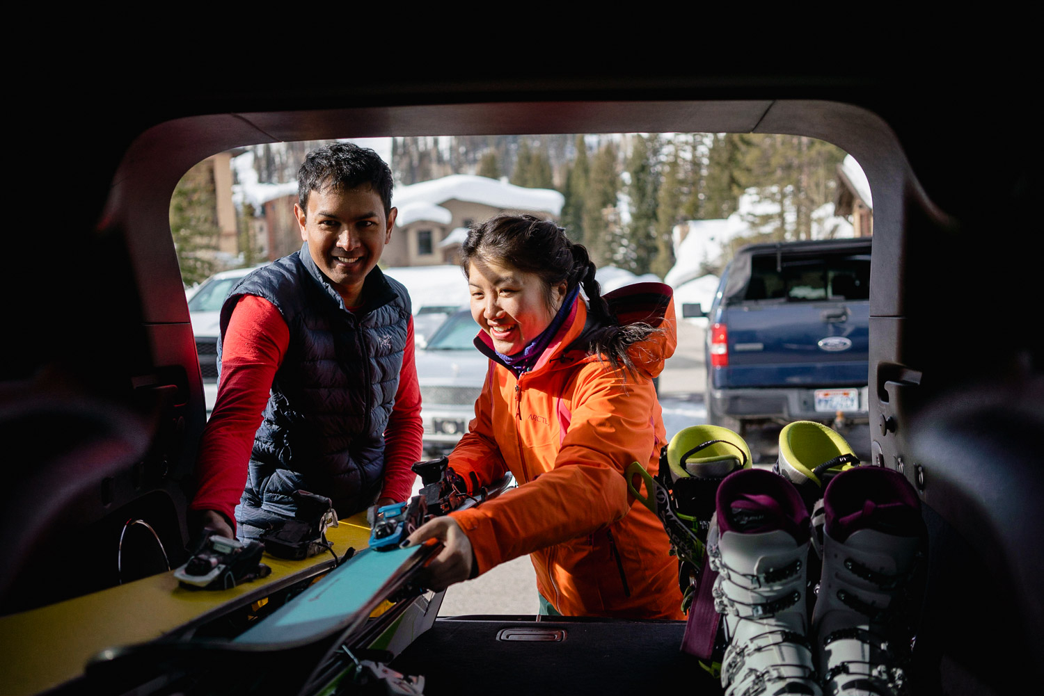 couple unloading skiis from car at utah resort