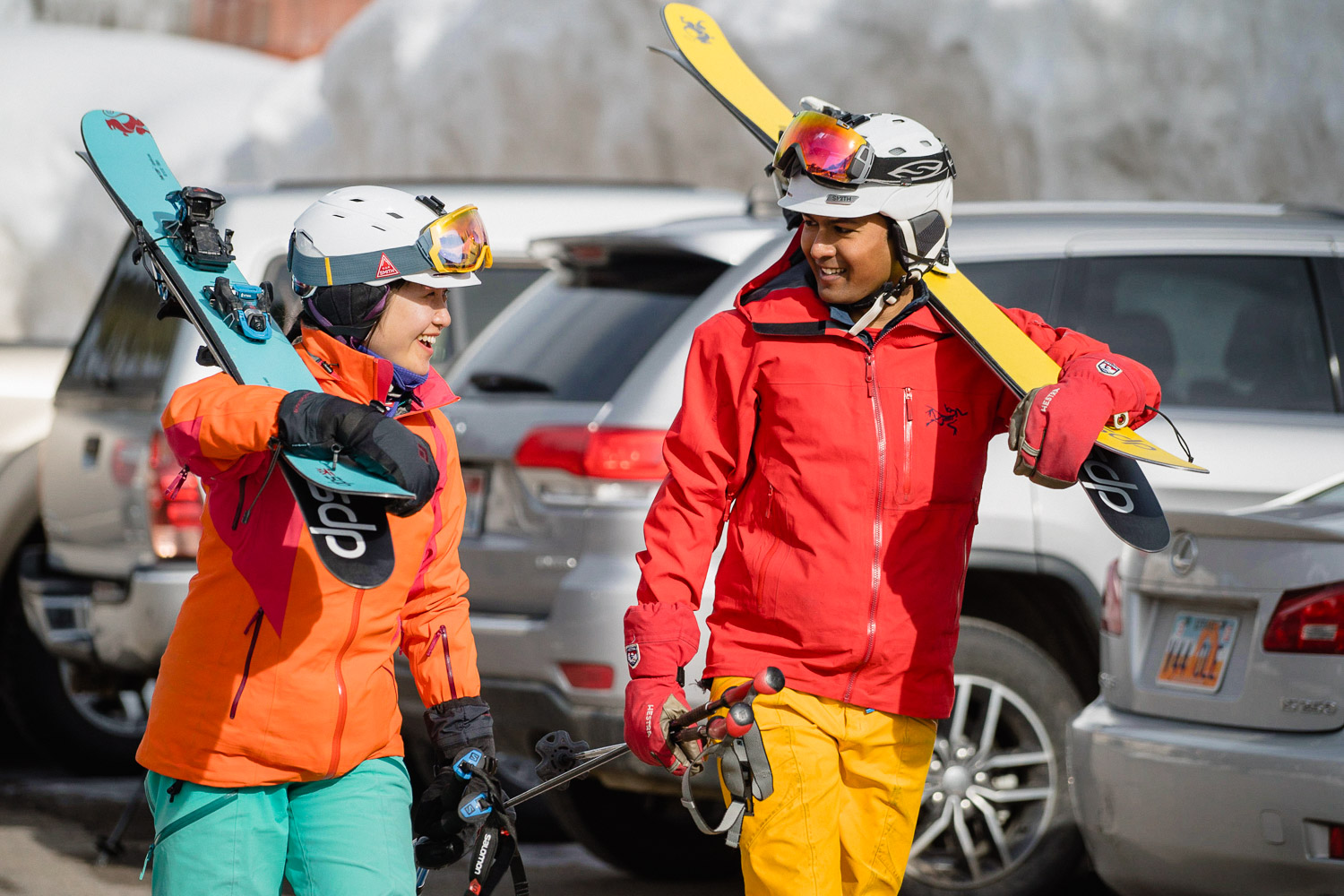 happy couple carrying skis in parking lot utah resort