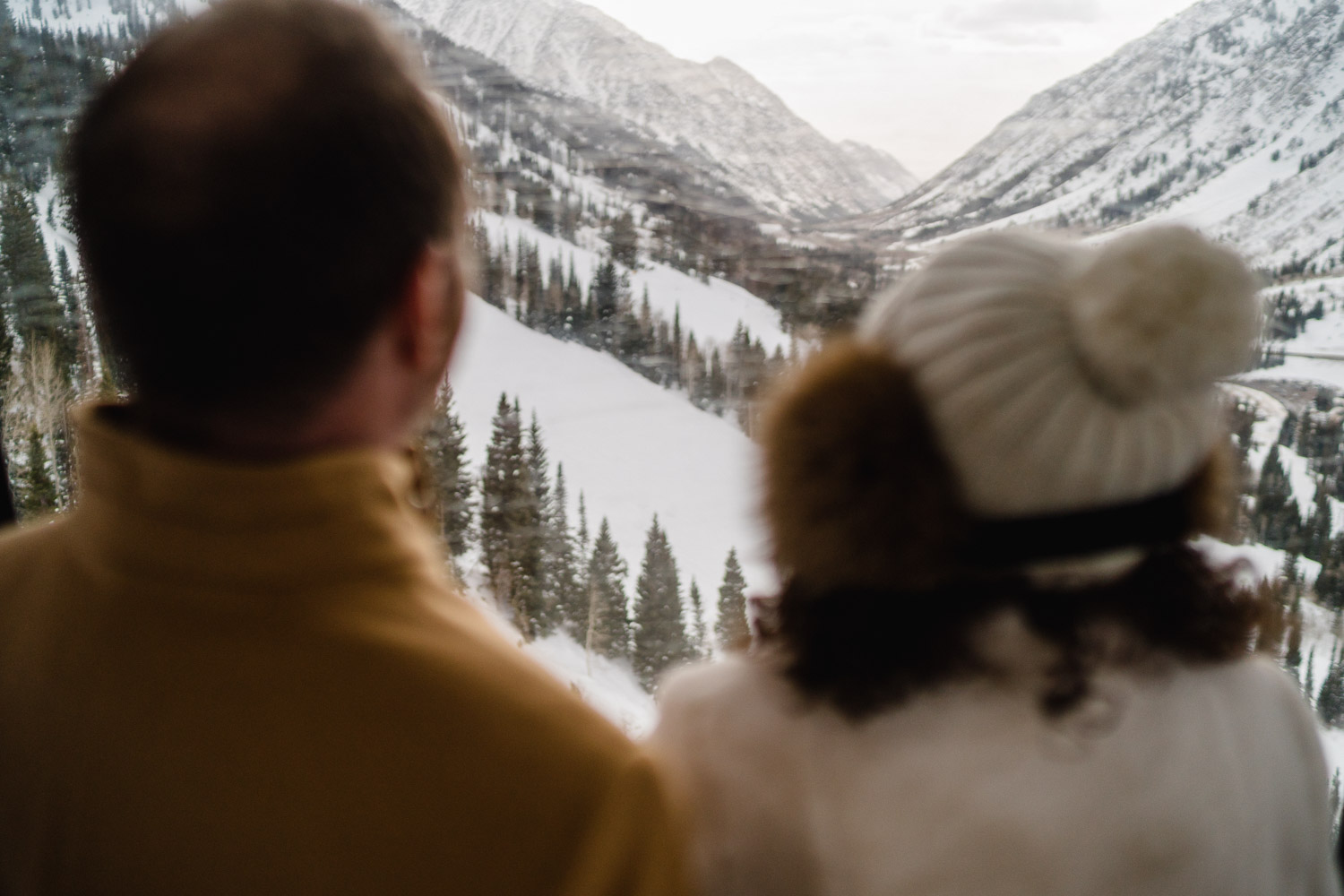 bride and groom look at mountain valley at snowbird resort