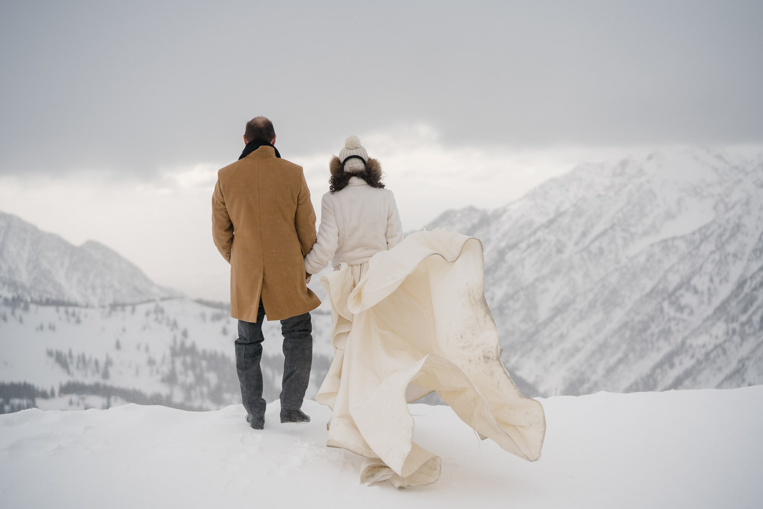 groom and bride with flowing train on snowy mountain snowbird resort