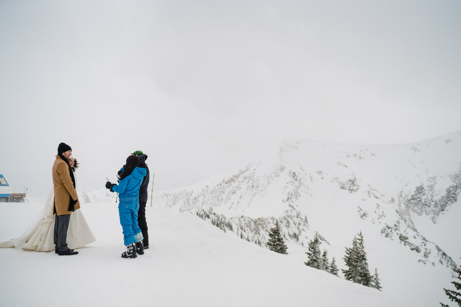 bride and groom with friends atop snowbird resort mountain top
