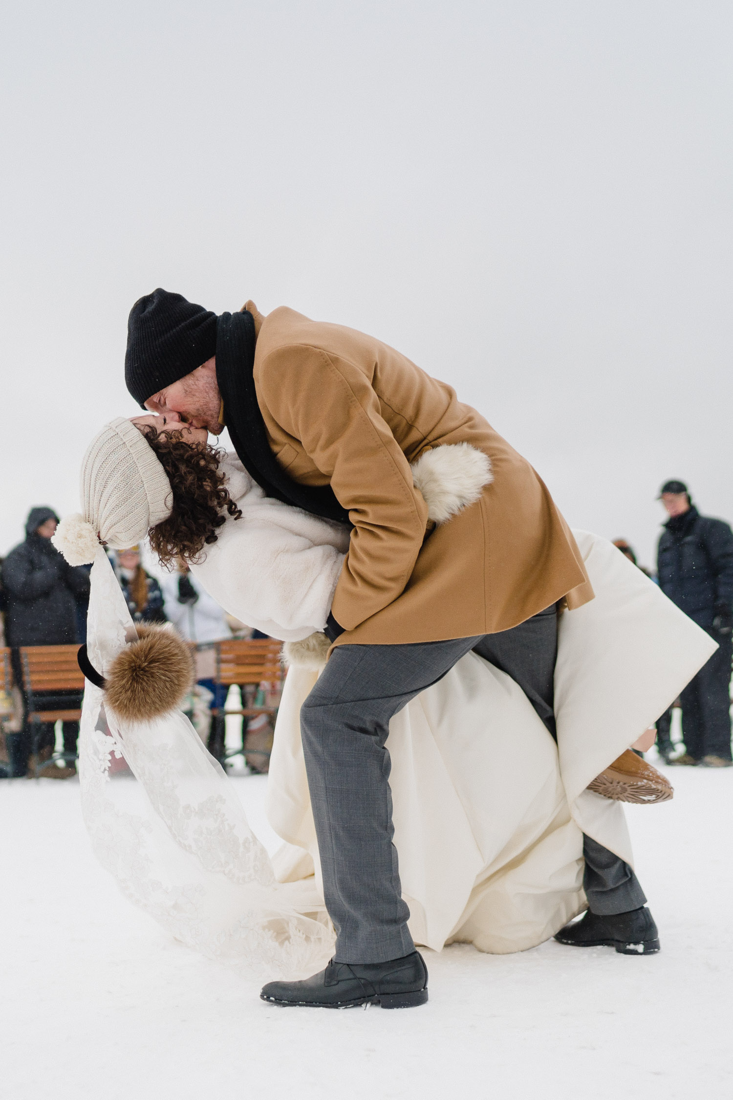 groom dipping and kissing bride on snowy mountain