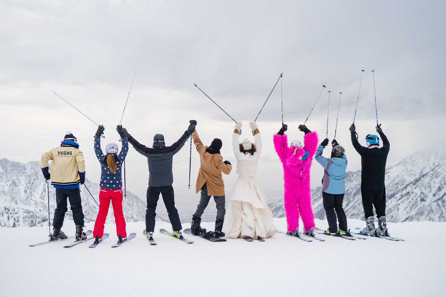 wedding party celebrating with poles up on snowy mountain top