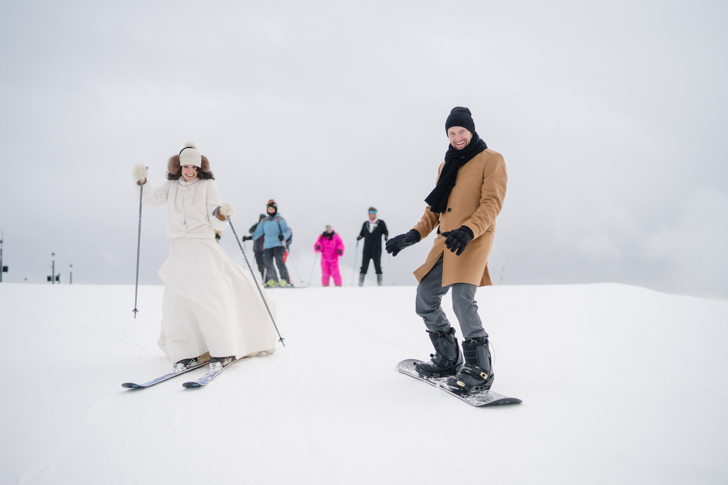 skiing bride with snowboarding groom on snowy mountain