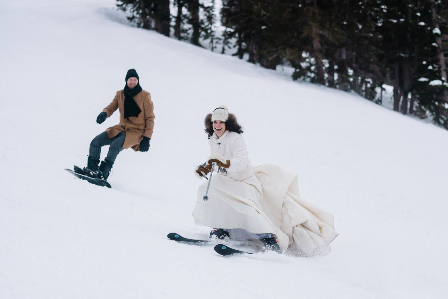 bride smiling and skiing with snowboarding groom at snowbird resort