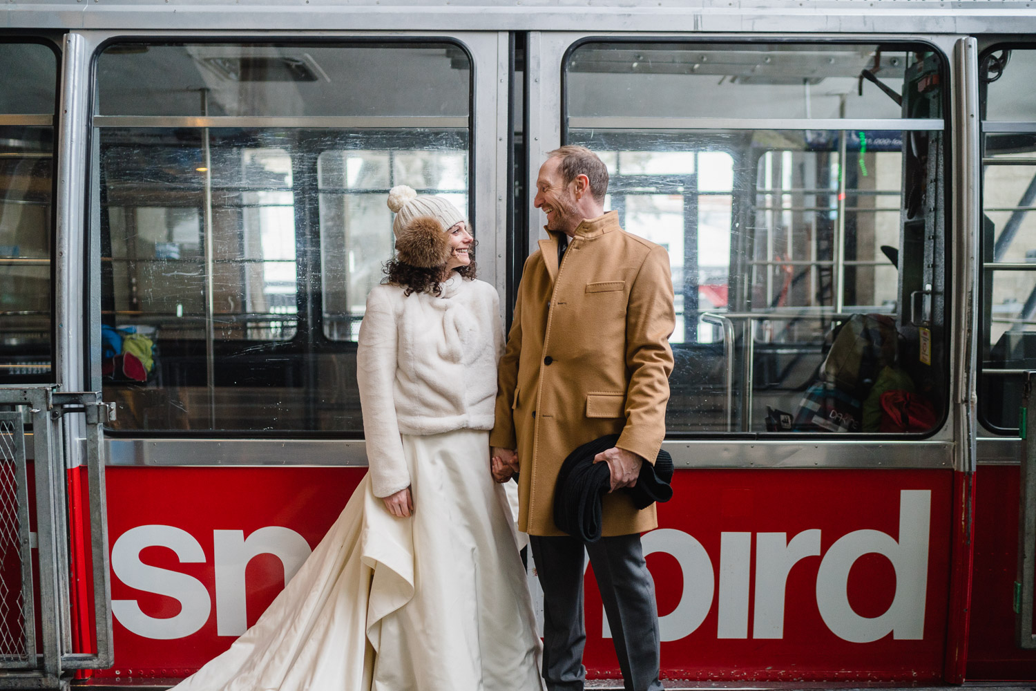 bride and groom smile at each other in front of snowbird tram